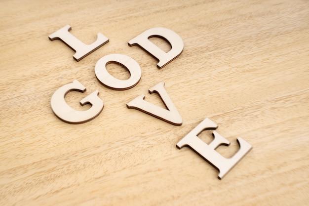 Dieu est le concept de l'amour. mots formant une croix sur une table en bois.