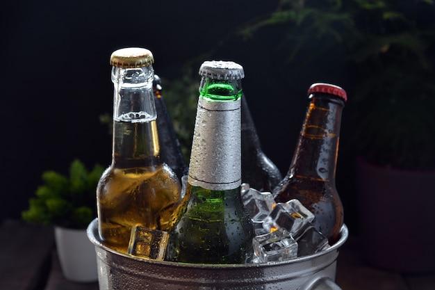 Différentes bières sur une table de bois. il y a une bouteille et un verre avec de la glace pour les garder au froid