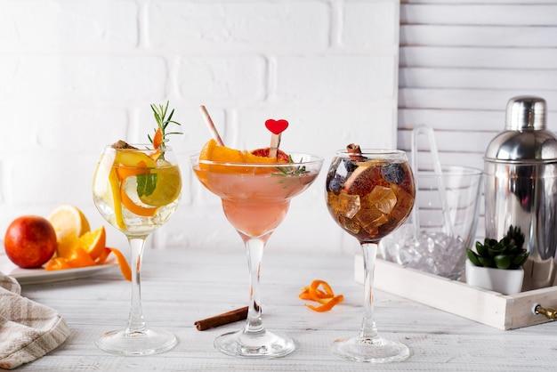 Différentes boissons alcoolisées en verre avec accessoires de bar sur fond en bois blanc