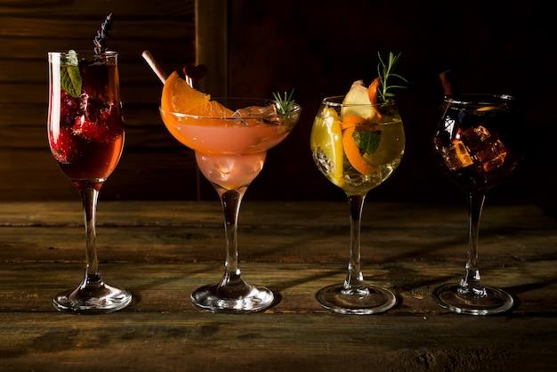 Différentes boissons alcoolisées en verre avec des fruits sur un fond en bois foncé