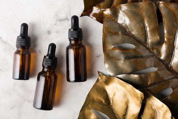 Différentes bouteilles d'huiles de soin sur fond de marbre