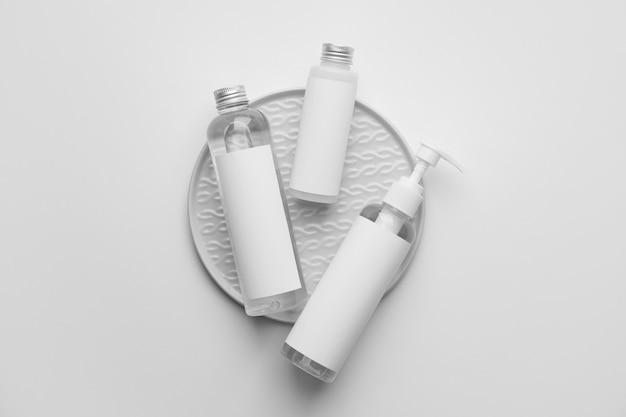 Différentes bouteilles de produits cosmétiques sur fond clair