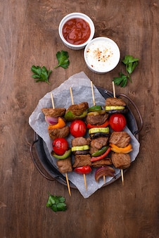 Différentes brochettes grillées avec viande, champignons, saucisses et légumes sur des brochettes