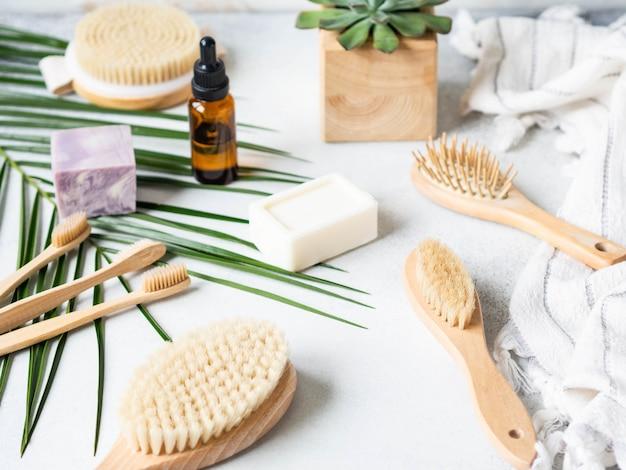Différentes brosses pour le corps, pierre ponce, brosse à dents en bambou, serviette blanche et un morceau de savon sur fond gris. concept zéro déchet. ensemble de bain écologique. espace copie