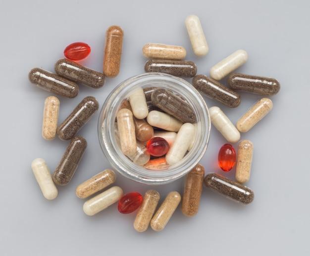 Différentes capsules médicinales se déversent d'un bocal en verre sur une surface claire