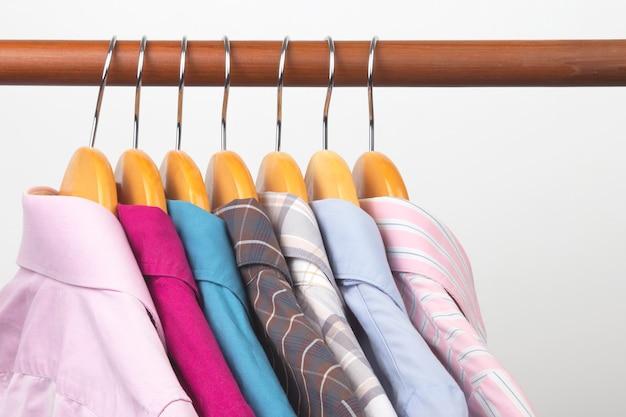 Différentes chemises classiques de bureau pour femmes sont suspendues à un cintre pour ranger les vêtements.