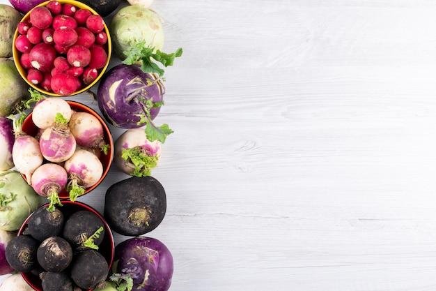 Différentes couleurs de radis frais dans quelques bols sur une table en bois blanc avec fond