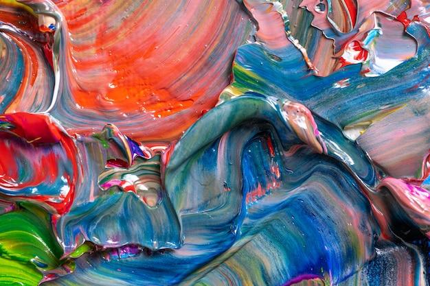 Différentes couleurs vives des peintures à l'huile sont mélangées dans une palette en gros plan.