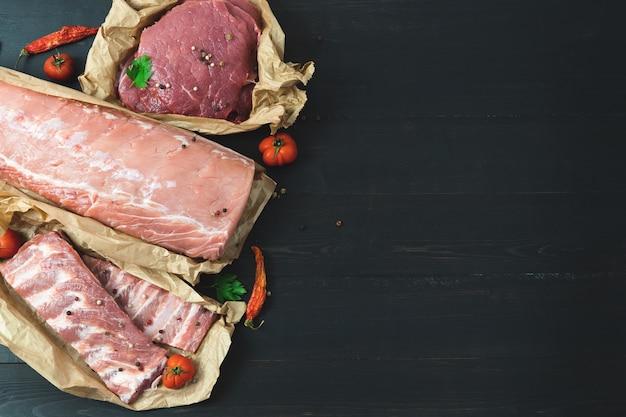 Différentes coupes de viande, fraîches sur fond sombre.