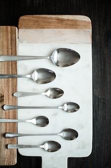 Différentes cuillères sur la surface de la table en bois en marbre de pierre. tonification de couleur vintage rustique