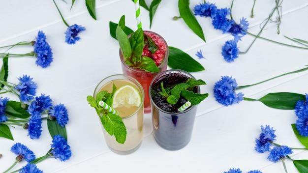 Différentes délicieuses limonades de fruits frais avec de l'eau pétillante sur fond blanc bois