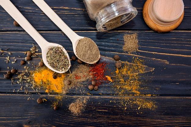 Différentes épices dans des cuillères en bois sur un fond en bois.