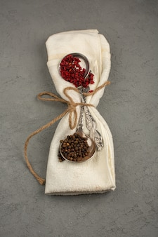Différentes épices rouge et brun épicé chaud sur une serviette crème sur un sol gris