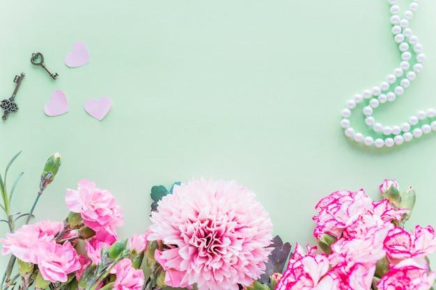 Différentes fleurs roses avec des coeurs sur la table verte