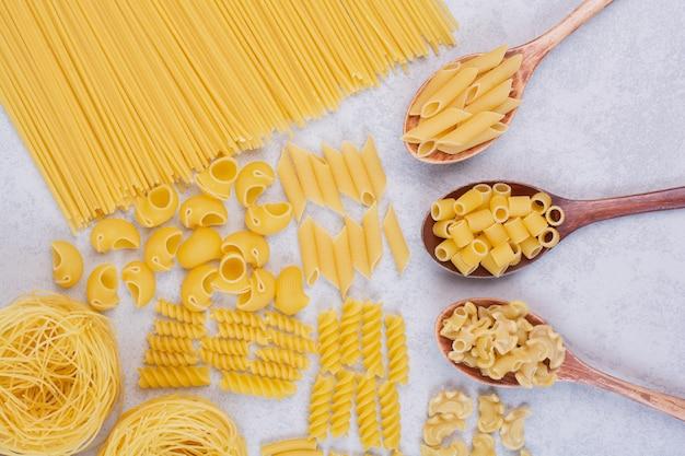 Différentes formes de pâtes et cuillères crues sur une surface blanche