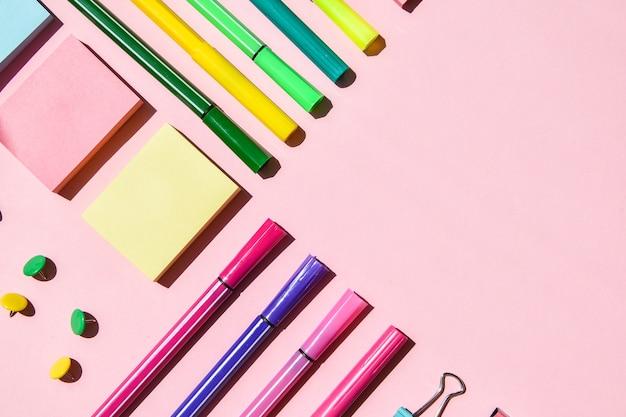 Différentes fournitures de bureau ou scolaires sur rose