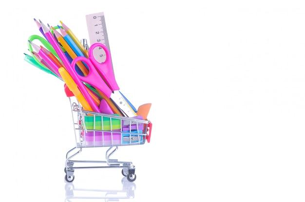 Différentes fournitures scolaires colorées dans un caddie sur un fond blanc isolé