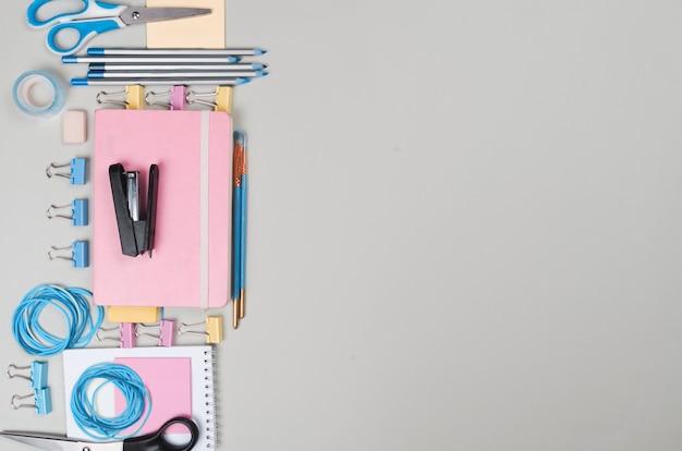 Différentes fournitures scolaires colorées sur l'espace background.copy gris clair