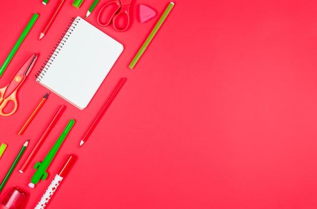 Différentes fournitures scolaires colorées sur fond de papier rouge