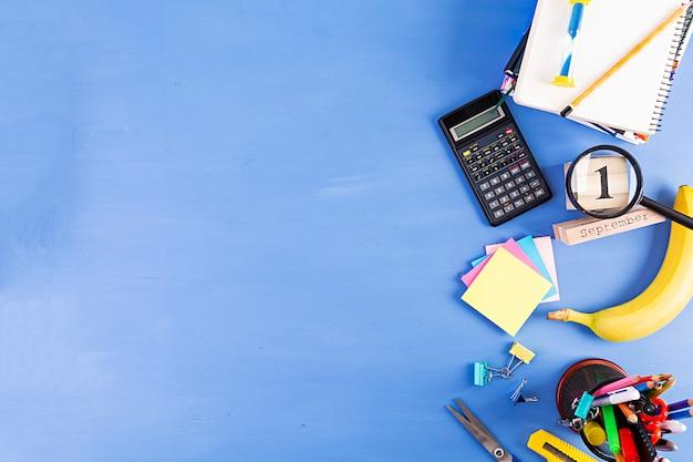 Différentes fournitures scolaires sur fond bleu. retour à l'école