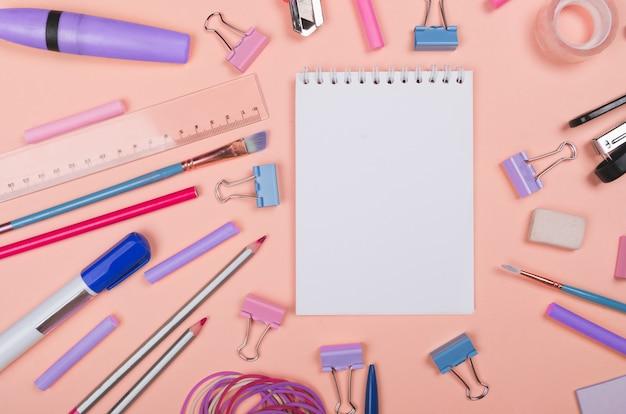 Différentes fournitures scolaires sur fond rose clair avec espace de copie