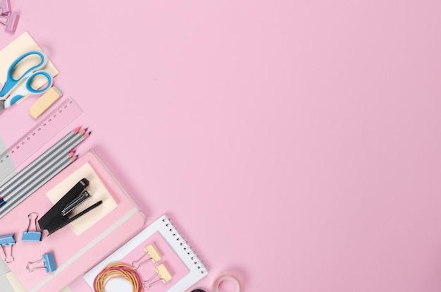 Différentes fournitures scolaires sur fond rose clair
