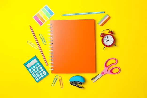 Différentes fournitures scolaires sur jaune