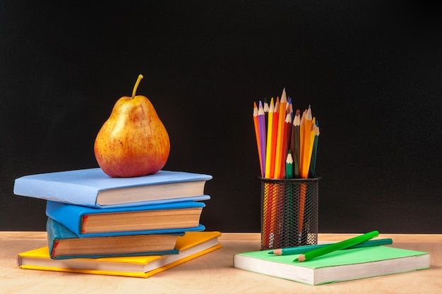 Différentes fournitures scolaires, des livres et des poires sur une table en bois