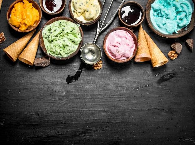 Différentes glaces aux fruits dans des bols avec des tasses à gaufres sur le tableau noir