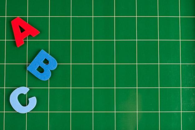 Différentes lettres se trouvent sur la surface verte du tableau noir