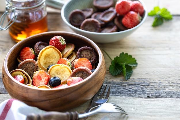 Différentes mini crêpes dans un bol en bois avec du miel et des bleuets sur une table en bois.