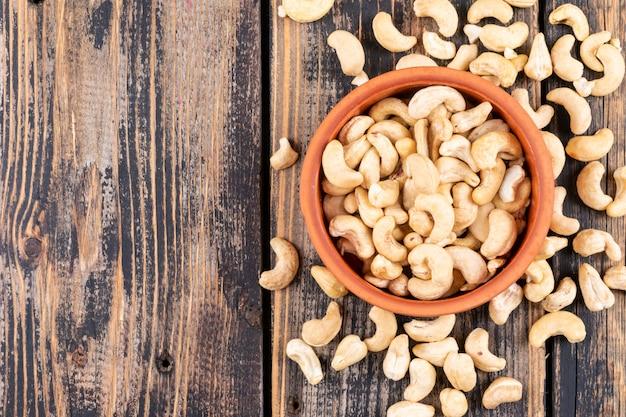 Différentes noix de cajou sur table en bois, vue de dessus.