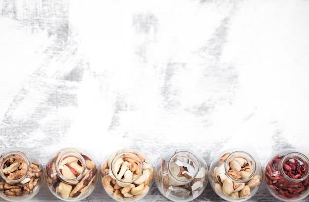 Différentes noix dans de petits pots sur un fond en bois clair, un concept d'aliments sains
