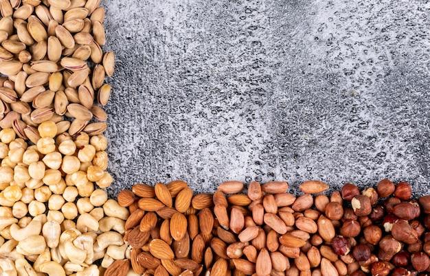 Différentes noix avec noix de pécan, pistaches, amande, arachide, noix de cajou, noix de pin vue de dessus