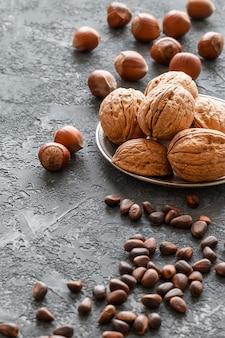 Différentes noix sur la table en pierre sombre. noisettes, noix, cèdre