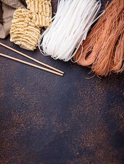 Différentes nouilles de riz asiatiques sur fond rouillé