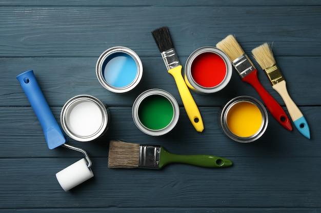 Différentes peintures, pinceaux et rouleaux sur une surface en bois