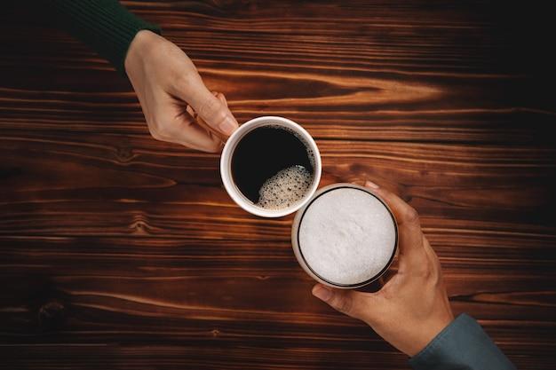 Différentes personnalités goûtent dans les boissons du concept de personnes, deux amis tenant une tasse de café chaud et un verre de bière pour faire des acclamations,