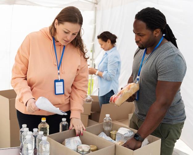 Différentes personnes faisant du bénévolat dans une banque alimentaire