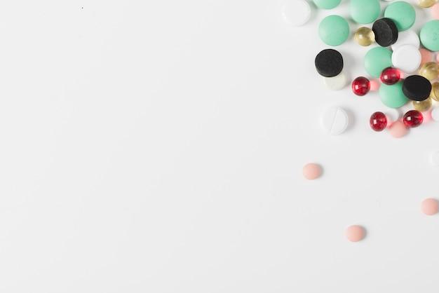 Différentes pilules colorées sur blanc