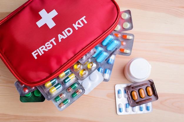Différentes pilules colorées dans une trousse de premiers soins
