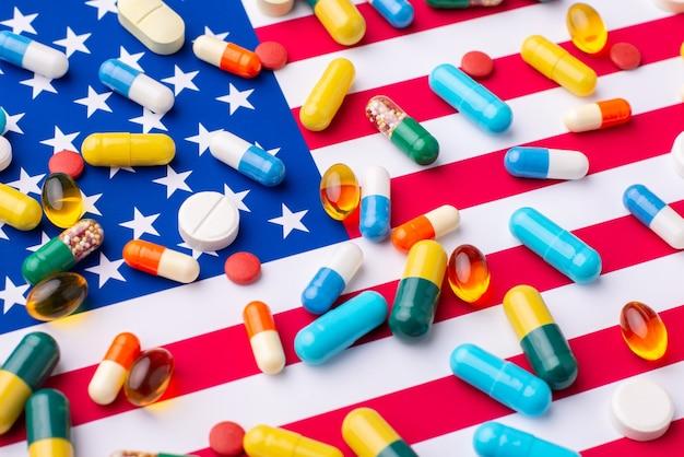 Différentes pilules et comprimés sur le drapeau des états-unis