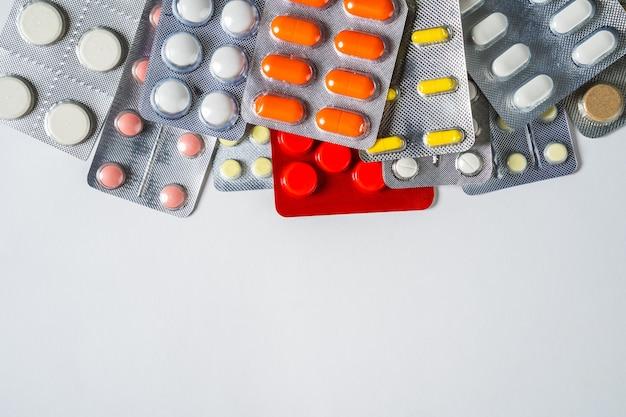Différentes pilules sur fond blanc.