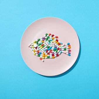 Différentes pilules et suppléments comme nourriture sur une plaque blanche ronde sous forme de poisson sur un mur bleu. pilules amaigrissantes et suppléments pour le concept de régime. mise à plat