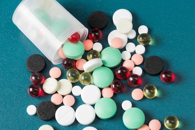 Différentes pilules et tasse en plastique