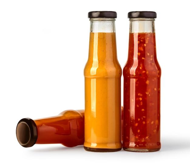 Les différentes sauces barbecue dans des bouteilles en verre isolated on white