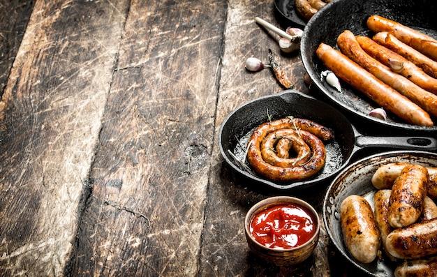 Différentes Saucisses Dans Des Casseroles Avec Sauce Tomate. Sur Un Fond En Bois. Photo Premium