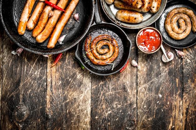 Différentes Saucisses Dans Des Casseroles Avec Sauce Tomate Sur Un Fond En Bois Photo Premium