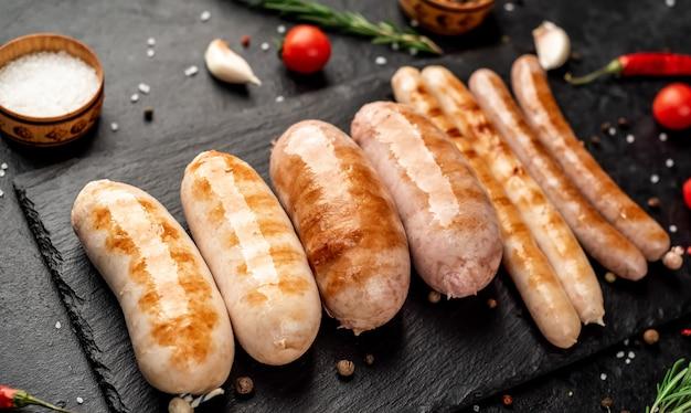 Différentes saucisses grillées aux épices et romarin servi sur une planche à découper sur un fond de pierre avec copie espace pour votre texte