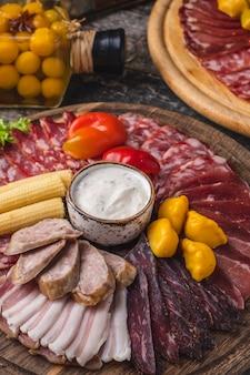 Différentes saucisses et légumes marinés sur planche de bois dans un style rustique. fermer